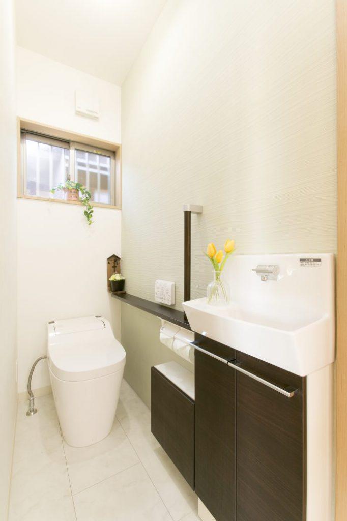 トイレ内ユニットタイプの手洗いは、収納と手すりが一体となった機能的仕様。ダークな木目をアクセントに白を基調とした、すっきりとしたトイレ空間です。